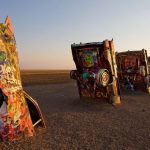 Half-buried, graffiti-decorated Cadillacs