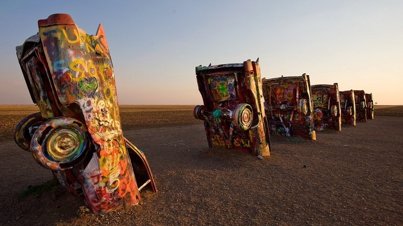 Half-buried, graffiti-decorated Cadillacs in a row