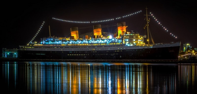 The Queen Mary lit up on the water at night