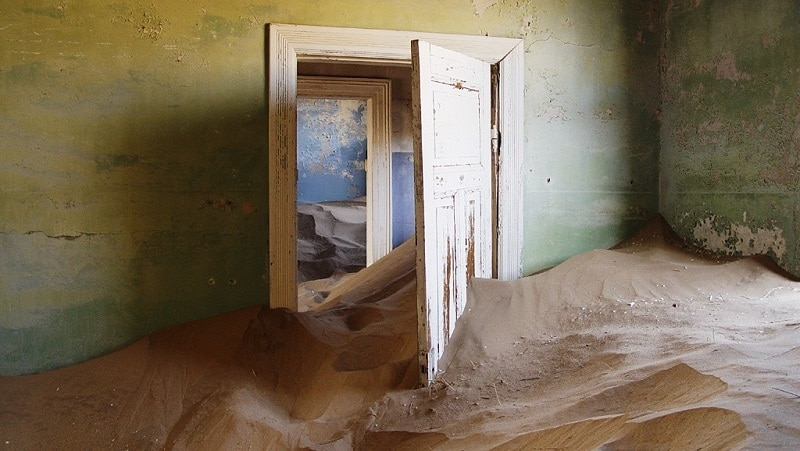 An abandoned room half-filled with sand