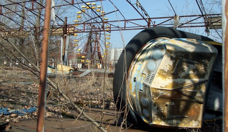Eerie scene of abandoned bumper cars and a ferris wheel in the amusement park at Pripyat