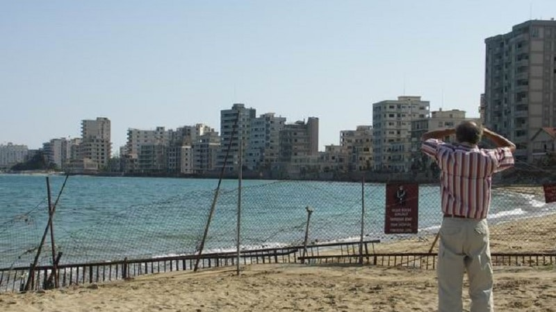 A man stares along the beach at the abandoned city of Varosha