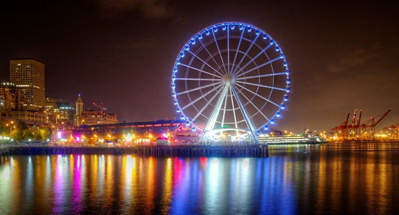 The Seattle Great Wheel lit up at night with downtown Seattle in the background