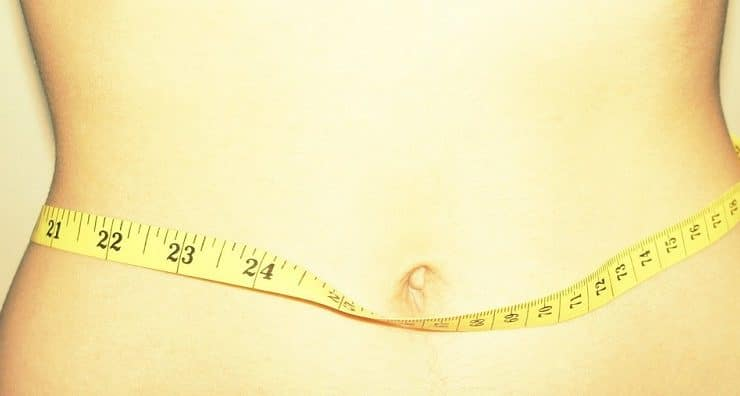 Close-up of a person's waist with a measuring tape wrapped around it