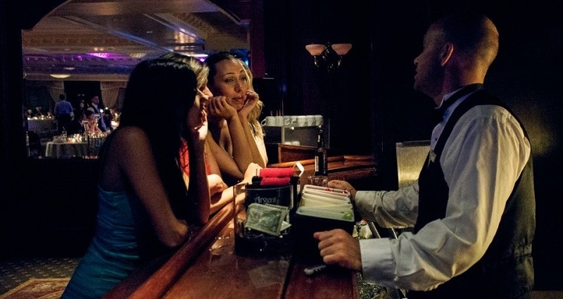 Male bartender talking to three female customers