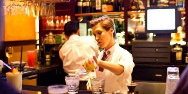 Bartender mixing drinks behind a bar