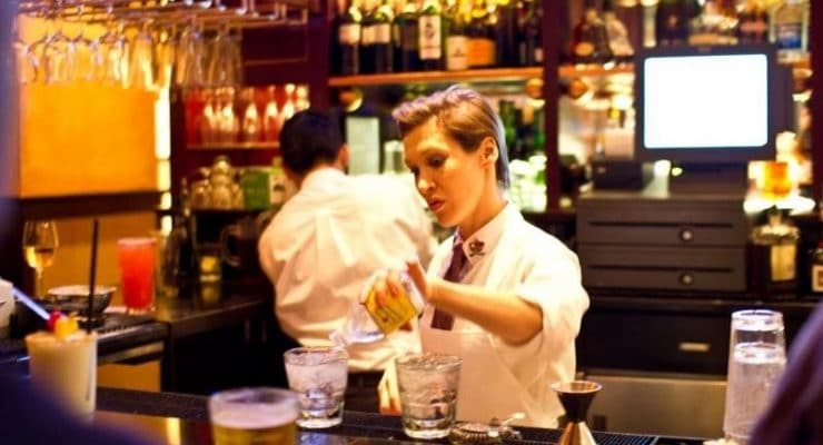 Bartender mixing drinks behind a bar