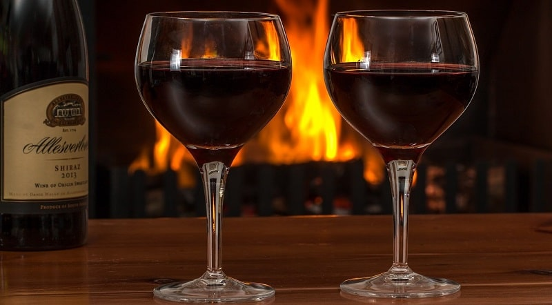 Two glasses of red wine in front of a fire
