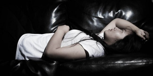 A lady lies on a sofa with her arm across her head, looking anxious