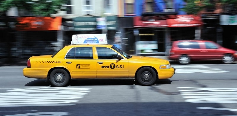 A yellow NYC taxi driving along a busy street
