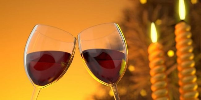 Two glasses of red wine with candles in the background