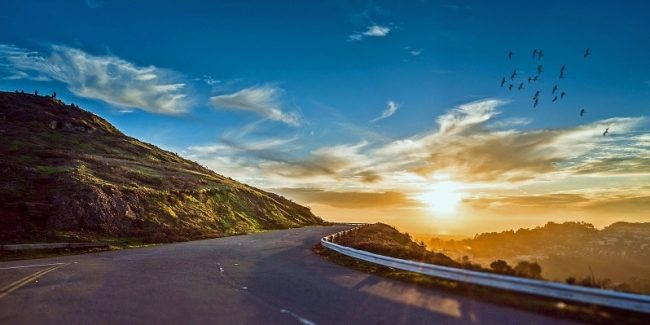 A mountain road with the sun setting in the distance