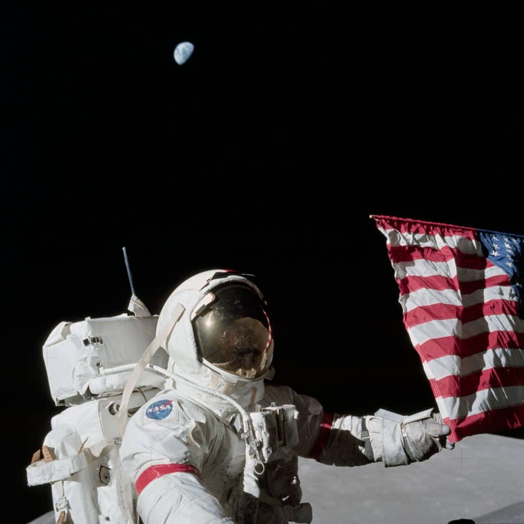 Commander Eugene A. Cernan holds the American flag during the Apollo 17 mission, the last time man set foot on the Moon