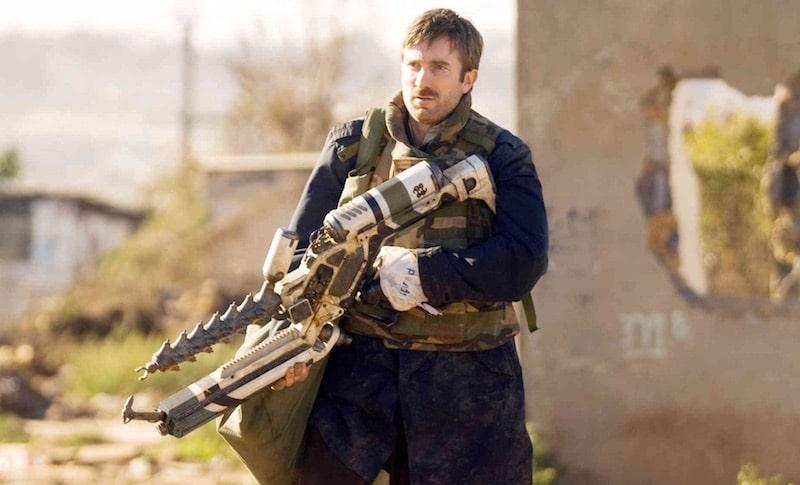 Protagonist Wikus van der merwe, played by Sharlto Copley, with an ARC gun in District 9