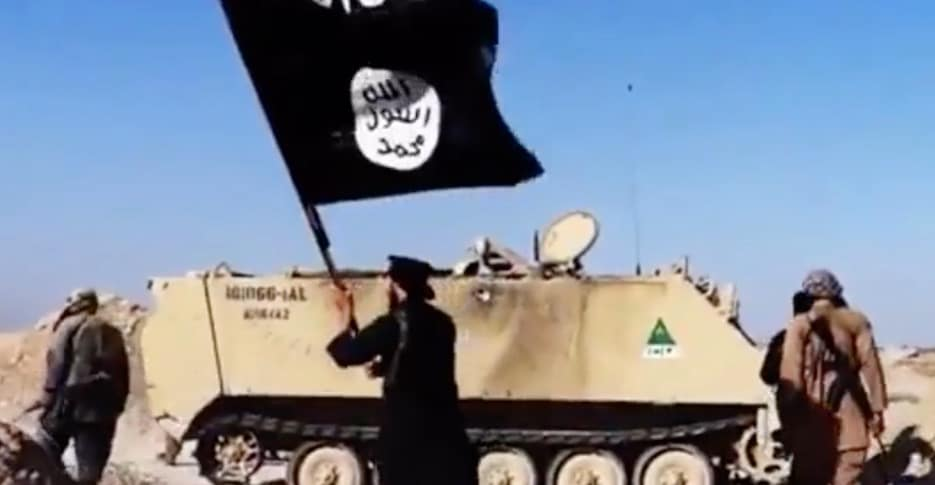 ISIS fighters with a captured amored vehicle