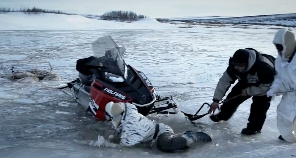 Chip falls through the ice as he tries to get his snowmobile out of the water.