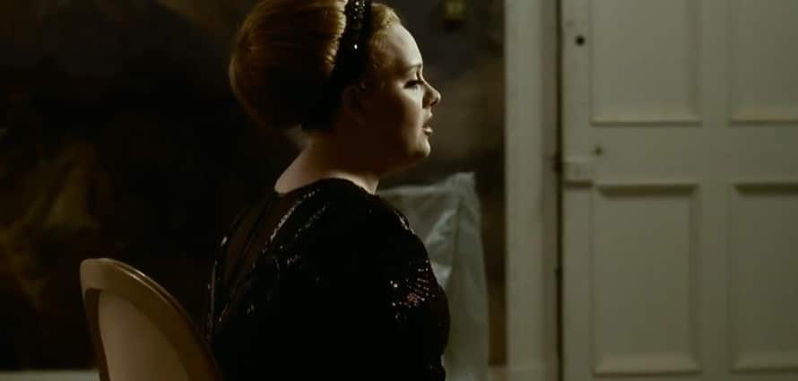 Adele singing in a music video, in profile
