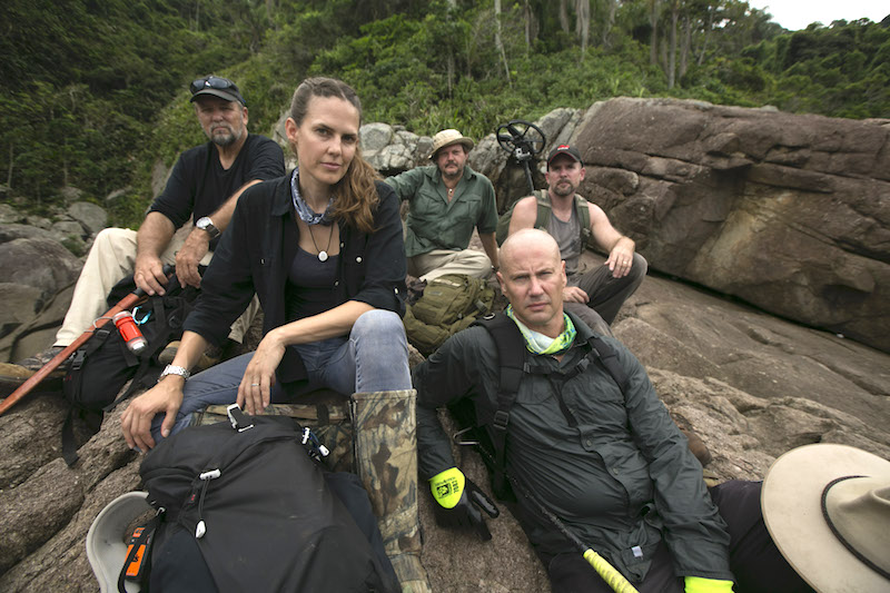 The team taking part in Treasure Quest: Snake Island Season 2 — Keith Plaskett, Cork Graham, Jeremy Whalen, Mehgan Heaney-Grier and Bryan Fry sitting on shore.