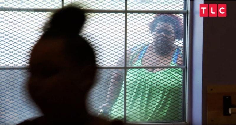 Cynthia watches Ukiah dance through a window