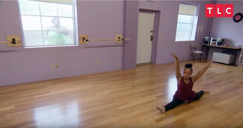 Ukiah dances while Cynthia watches through a window through a window