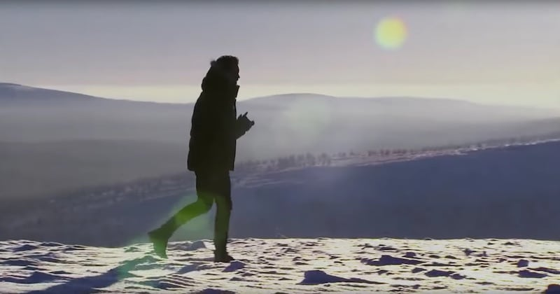 Nick walks through the snow with the sun low in the sky behind him