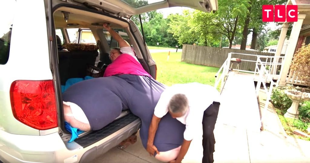 Tracey's husband Anthony lifts her hugely swollen legs into their car on My 600-lb Life