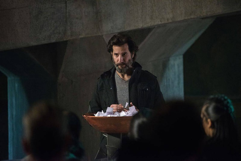 Kane holding a bowl containing pieces of paper on The 100