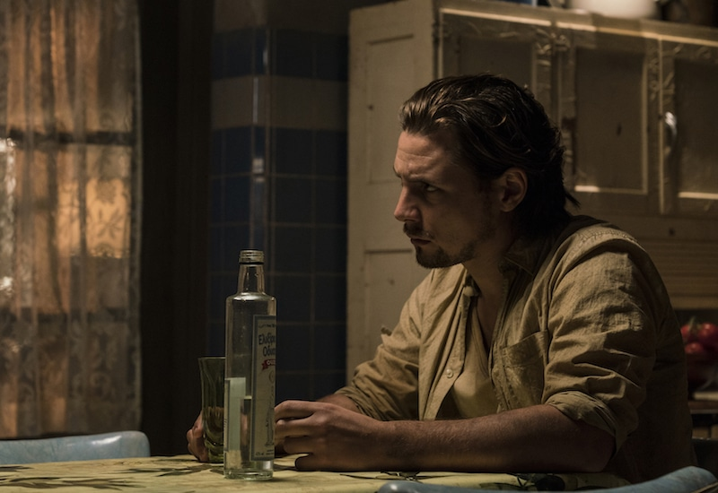A close-up of Whip looking at Lincoln with a glass in his hand and a bottle on the table