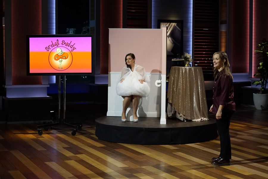 The model demonstrates going to the toilet with the Bridal Buddy slip wrapping her dress up