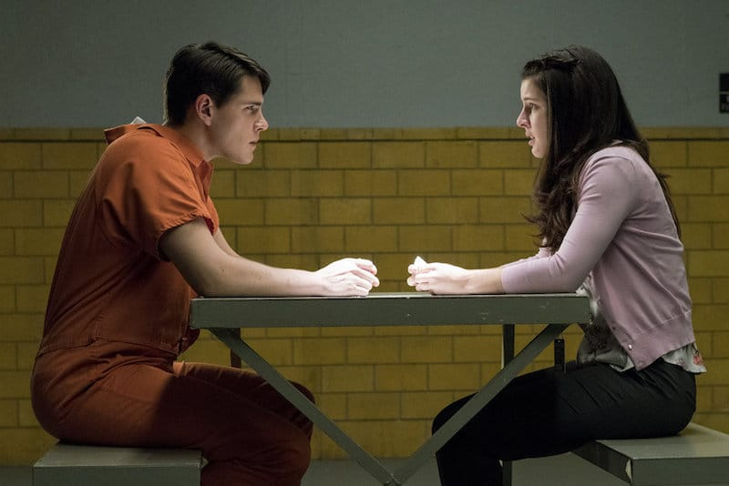 Characters Lucas Hale and Ann Davenport sitting opposite each other in a jail meeting room