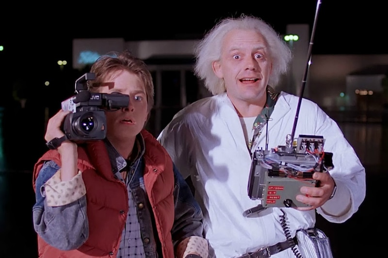 Christopher Lloyd standing next to Michael J. Fox in as till from the Back To The Future series