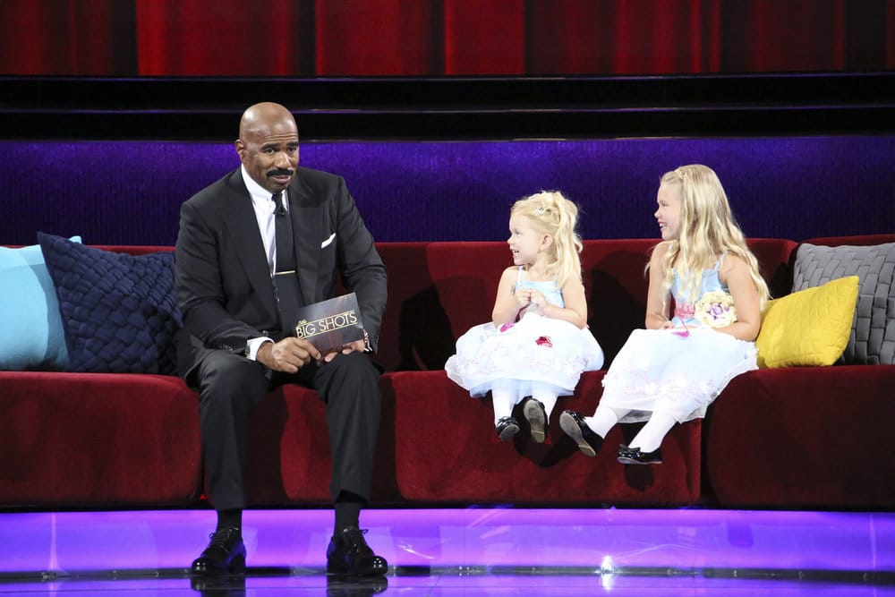 Grace and Giuliana sitting on a couch talking to Steve Harvey about their video on Little Big Shots