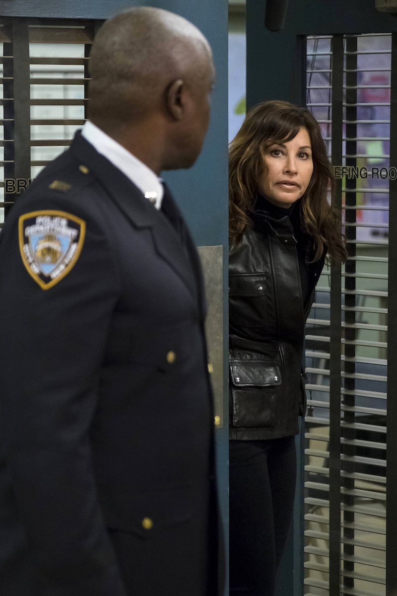 Andre Braugher's character Capt. Holt looks as Gina Gershon's character Lieutenant Melanie Hawkins walks through a door
