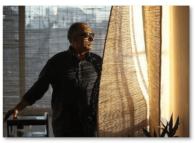 Abbas Kiarostami standing by a curtain looking out a window