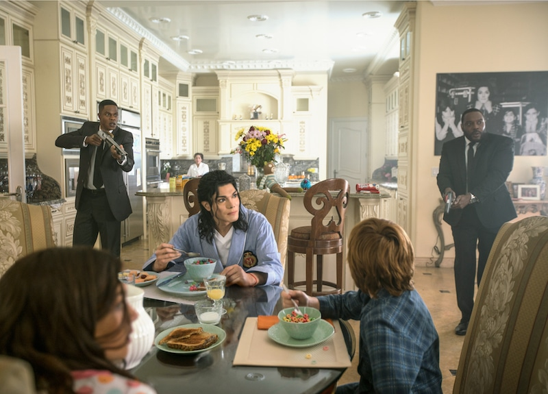 A scene from Searching for Neverland with Michael at breakfast with his kids, as two bodyguards stand behind him with guns drawn