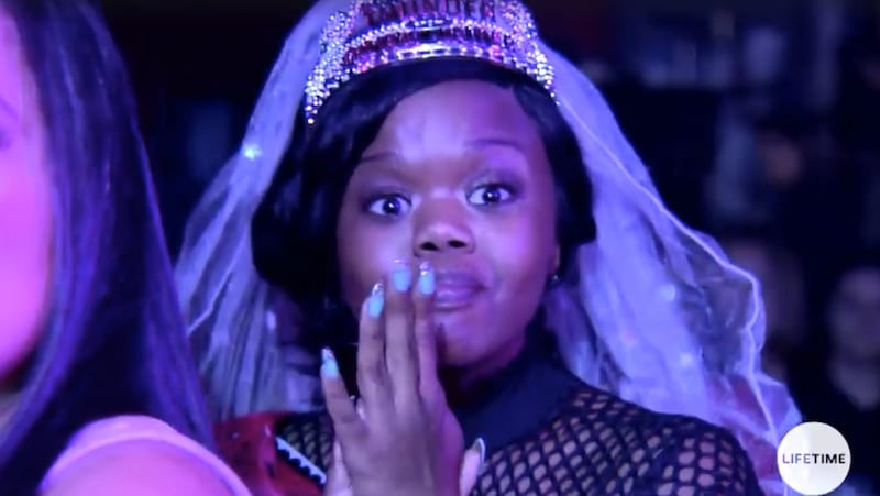 Little Women: Atlanta's Monie dressed in a veil watching strippers on stage