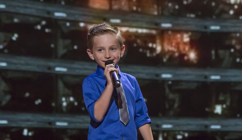 Nathan Bockstahler holding a microphone as he performs on Little Big Shots