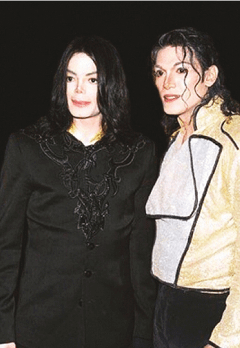 Photo of Michael Jackson standing next to his impersonator Navi