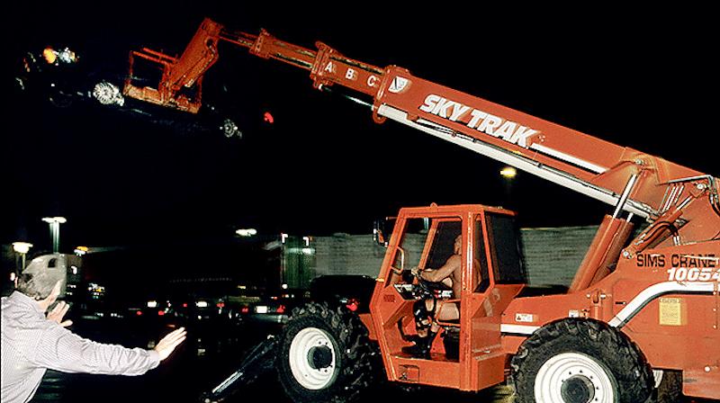 A crane driven by Stone Cold Steve Austin lifts a limousine