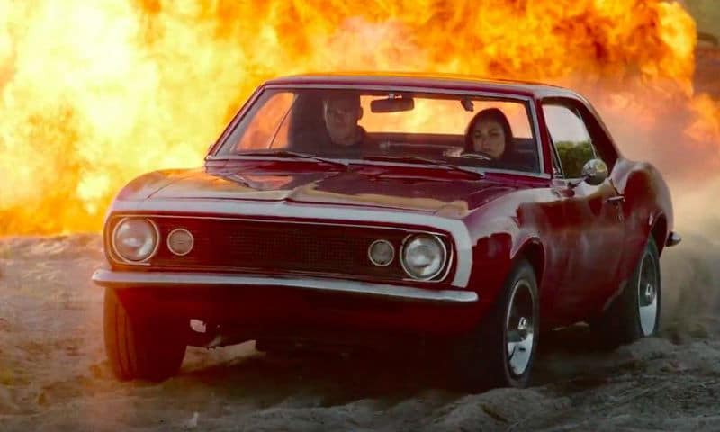 Arthur Bailey and Grace in a car with flames behind them