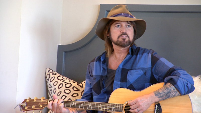Billy Race Cyrus sitting strumming a guitar on Billy Race Cyrus