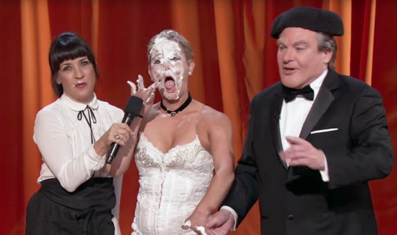 Mike Myers as Tommy Maitland standing next to a cake-eating opera singer on The Gong Show
