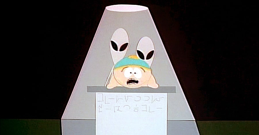 Cartman lying face down on a table as two aliens stand behind him