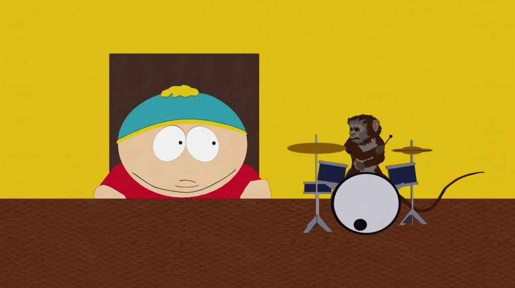 Cartman sitting at a desk with a monkey on top playing a tiny drum kit