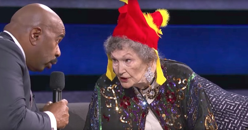 Bonnie Swalwell Eilert demonstrating her animal calls to Steve Harvey while wearing a chicken hat