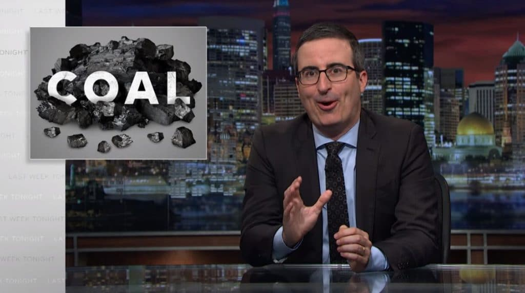 John Oliver talks to the camera with a picture of coal on the screen behind him
