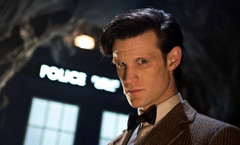 Matt Smith looking down at the camera while standing in front of the TARDIS