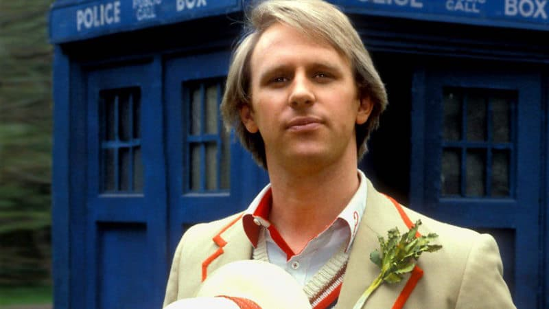 Peter Davison wearing his cricket-like attire and standing in front of a TARDIS