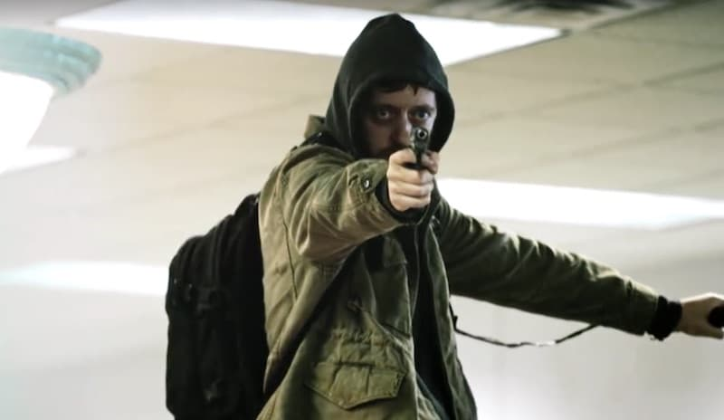 An actor playing Clifford Lynn Draper as he stands on a table pointing a gun at hostages