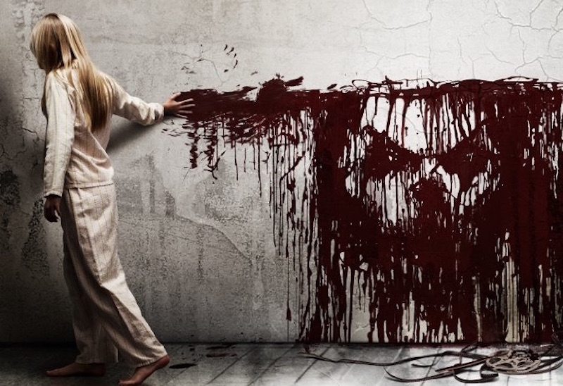 A woman wipes blood along a wall, with the drips forming a creepy face, in artwork from Sinister
